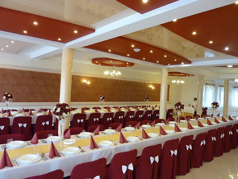 sala weselna zprzygotowanymi dwoma rzędzami stołów