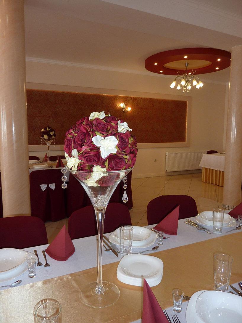 dekoracja kwiatami stołu weselnego wwysokim wazonie