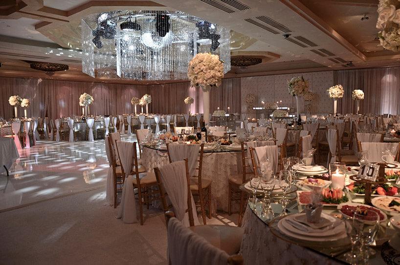 udekorowana iprzygotowana sala weselna zcentralnym dużym żyrandolem