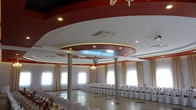 duża sala weselna ze stołami ustawionymi pod dwoma ścianamy