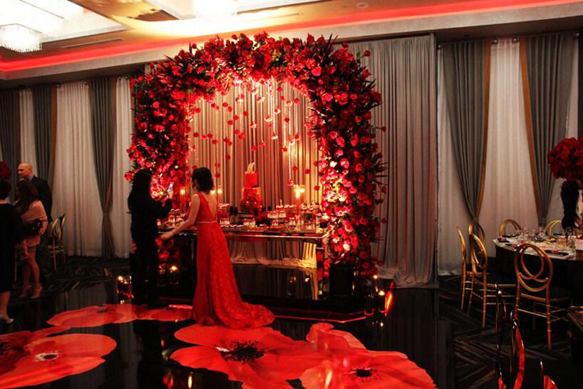 stół zprzystawki ozdobiony łukami ozdobionymi czerwonymi różami
