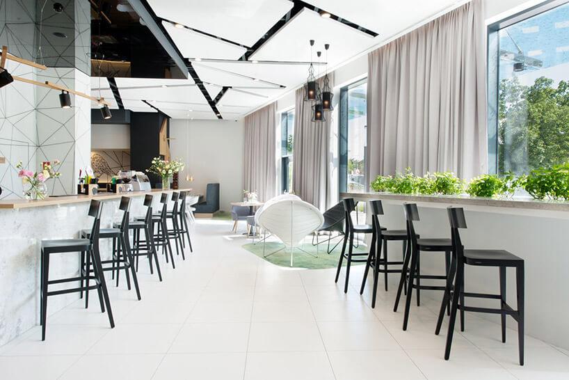 białe wnętrze restauracji zczarnymi krzesłami