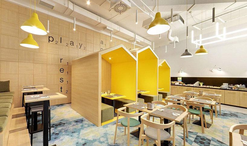 wnętrze restauracji ztrzema zabudowanymi stolikami