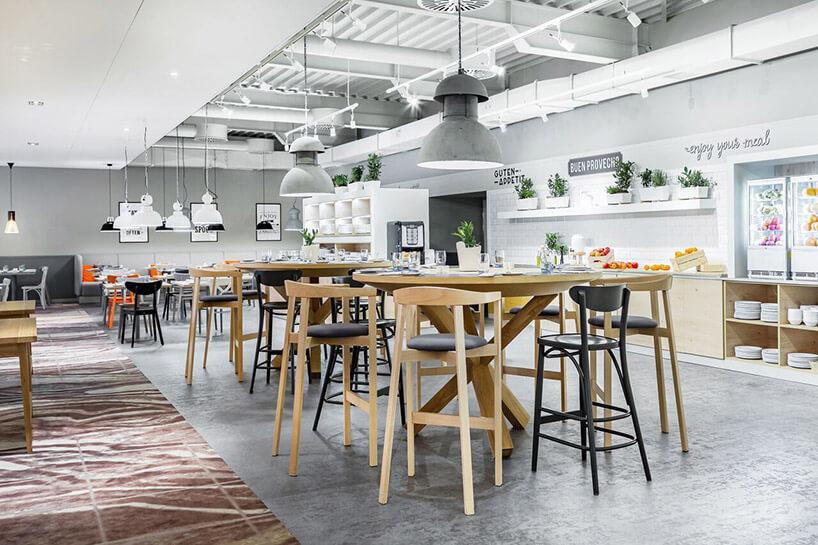 białe wnętrze restauracji zdrewnianymi stolikami ikrzesłami