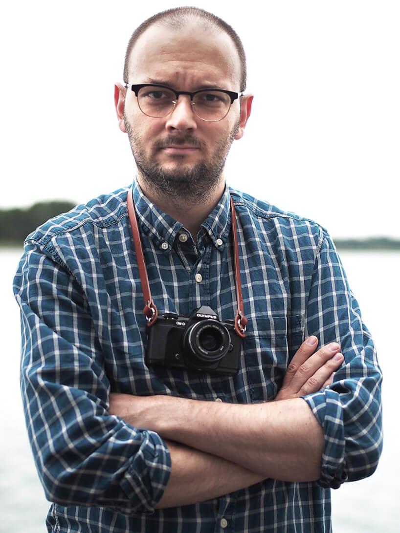 zdjęcie Filip Springer zaparatem fotograficznym na szyj