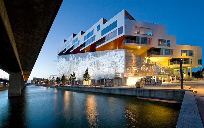 nowoczesny budynek nad wodą zczęściowo szklaną fasadą