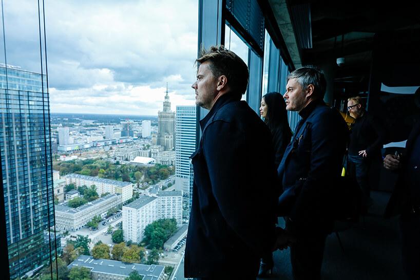 kilka osób przy oknach budynku na wysokim piętrze na tle panoramy Warszawy