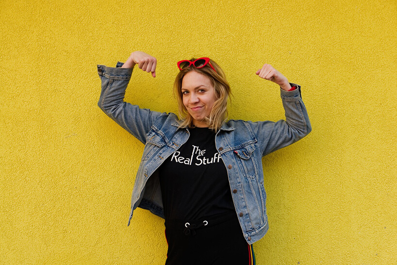 zdjęcie Arety Szpury wjeansowej kurtce zczerwonymi okularami na głowie na tle żółtej ściany