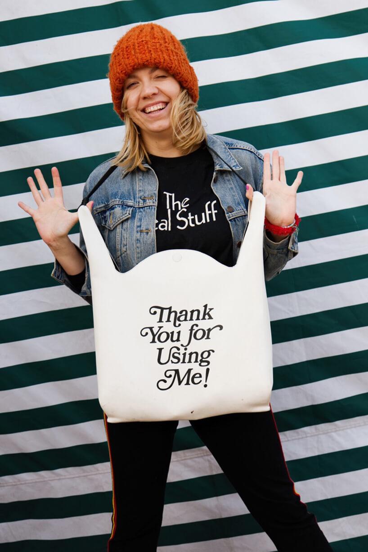zdjęcie Arety Szpury wjeansowej kurtce wczerwonej czapce trzymającą białą torbę znapisem Thank You for Using Me!