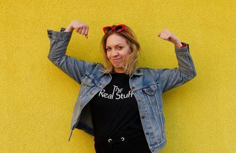 zdjęcie Arety Szpury w jeansowej kurtce z czerwonymi okularami na głowie na tle żółtej ściany