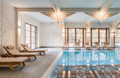 basen z niebieską wodą oraz drewnianymi leżakami z materacami w zamkniętym pomieszczeniu