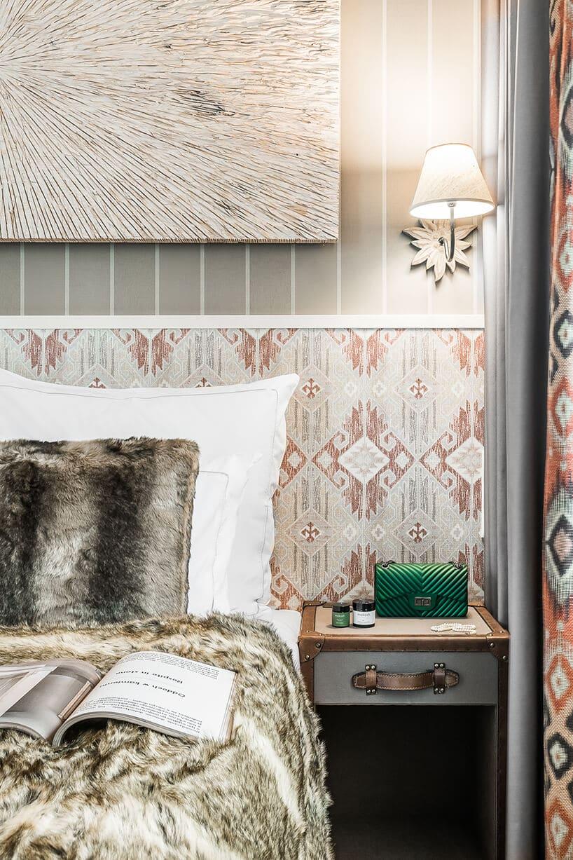 zagłowię łóżka zfutrzanym pościelą we wzory na tle tapety wbiałe paski