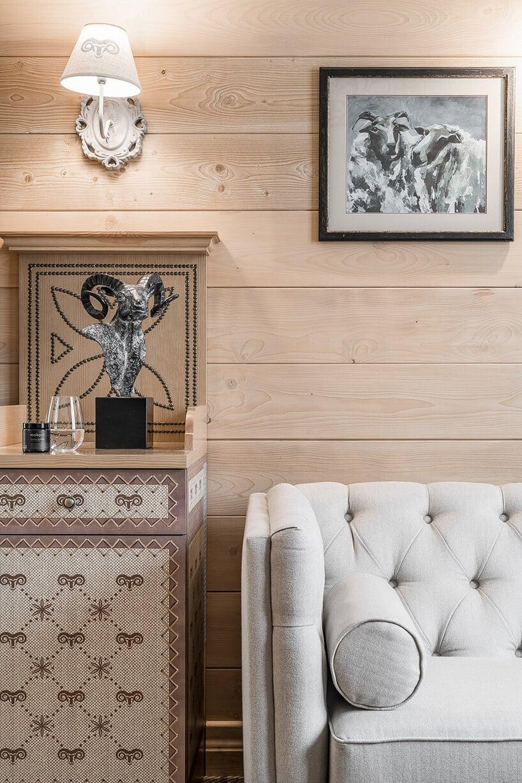 biała pikowana kanapa przy ścianie zdrewnianych paneli zobrazkami wramkach