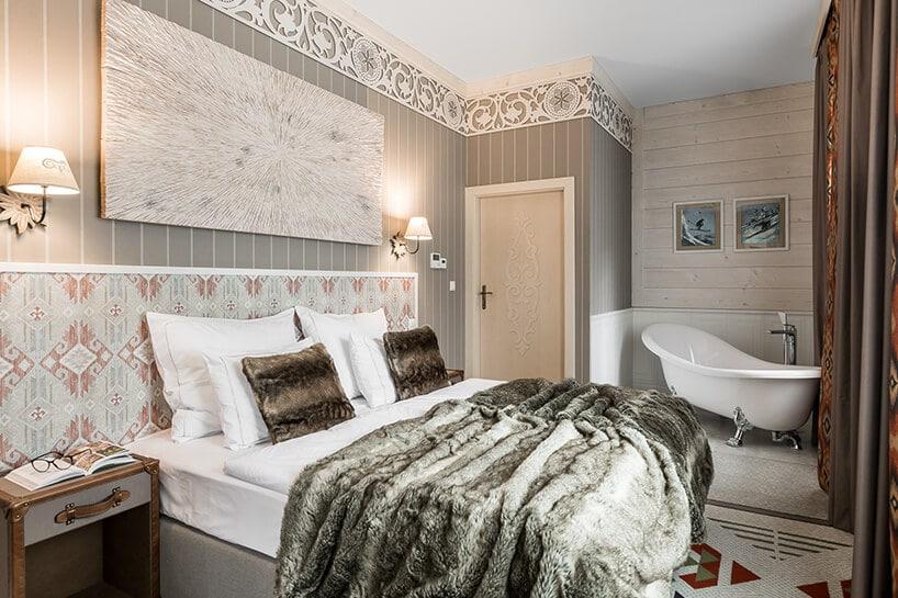 sypialnia zdużym łóżkiem małżeńskim oraz stykową retro wanną