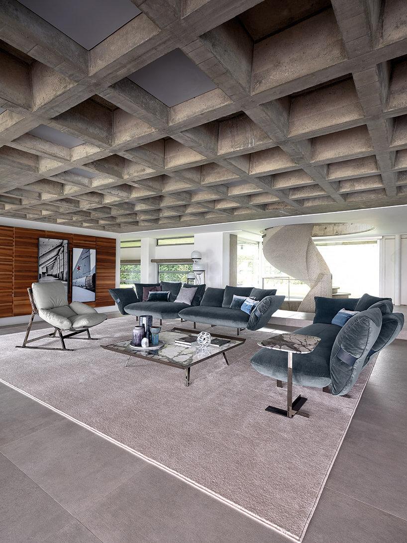 biały fotel niebieskie kanapy istolik na szarym dywanie