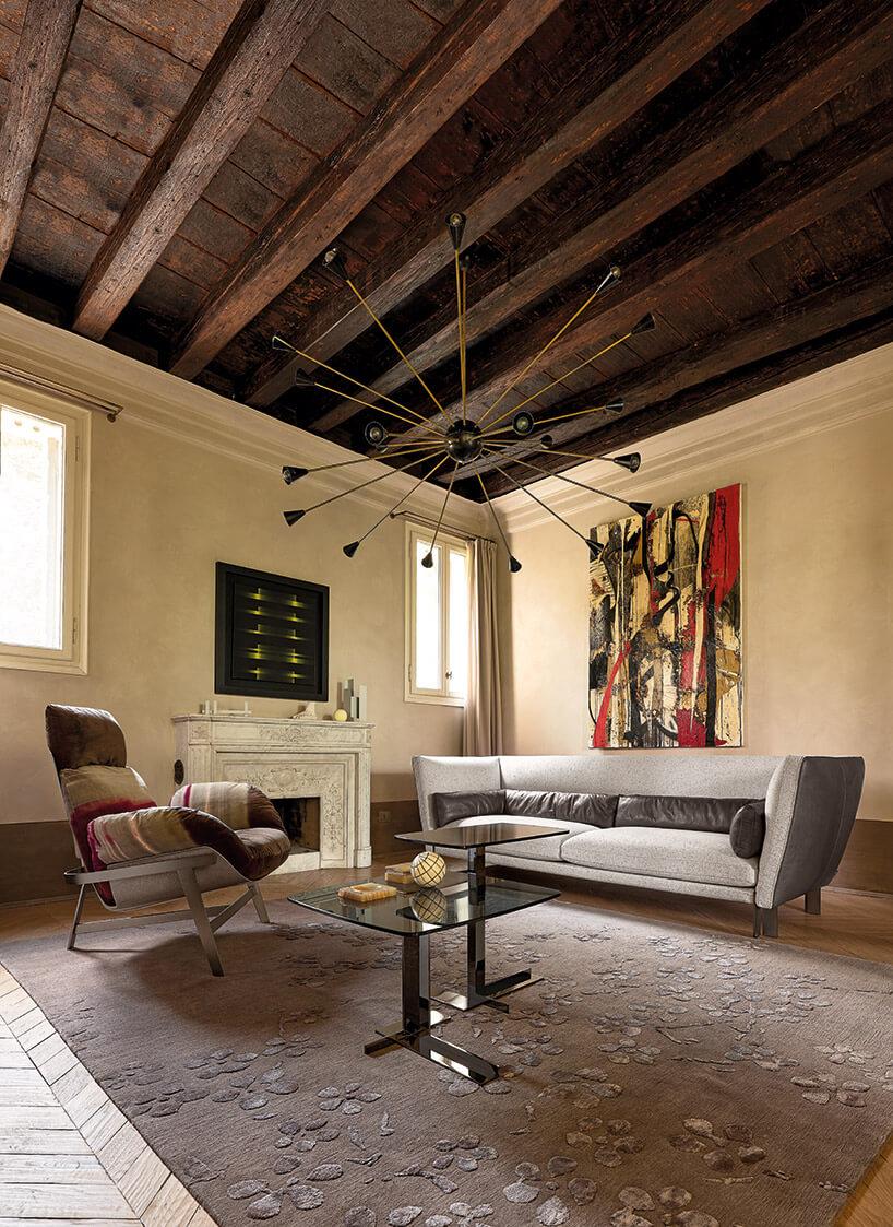 szara kanapa brązowy fotel iszklany stół na brązowym dywanie