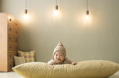 dziecko na jasnej poduszce na tle ściany i wiszących u góry lamp