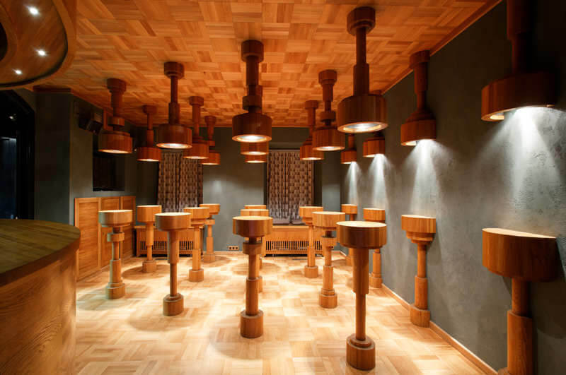 drewniane stoły przy szarych ścianach