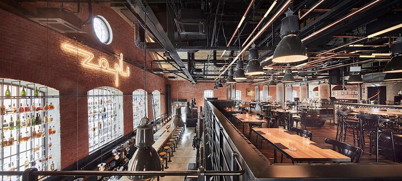 industrialne wnętrze restauracji Zoni widok zantresoli na ceglane mury iduże fabryczne okna