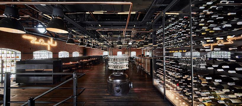 industrialne wnętrze restauracji Zoni czarna drewniana podłoga pod dużymi fabrycznymi lampami