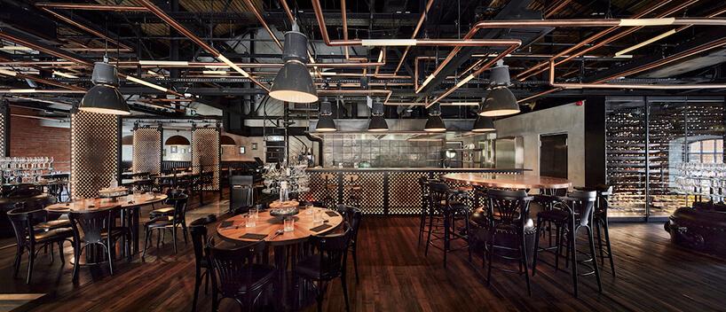 industrialne wnętrze restauracji Zoni eleganckie drewniane stoliki zczarnymi krzesłami na tle kuchni