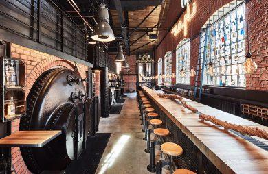 industrialne wnętrze restauracji Zoni z długim drewnianym barem na tle ceglanej ściany