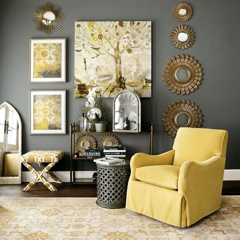 żółty wygodny fotel wprzy ciemnoszarej ścianie zobrazami