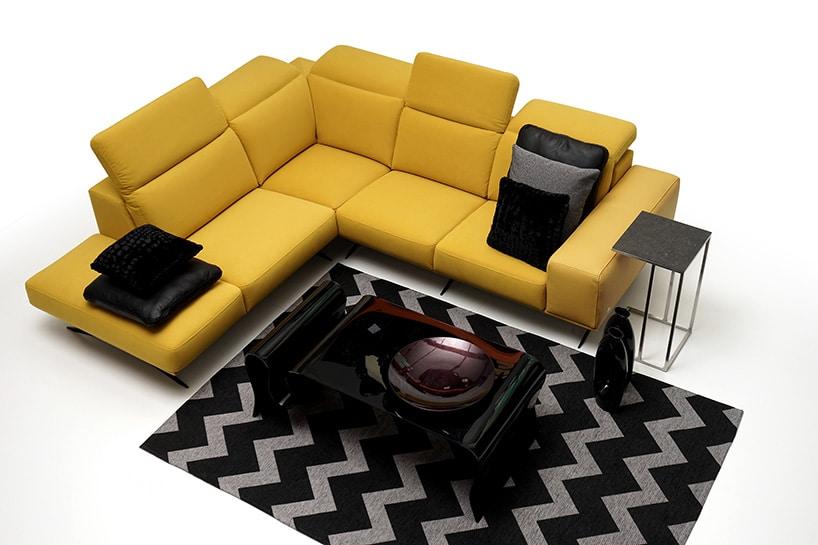 kanarkowo żółta kanapa wliterę Lzczarnymi poduszkami iciemnym dywanem ze wzorem