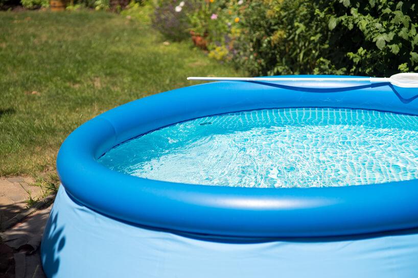 niebieski duży dmuchany basen na zielonej trawie wogrodzie
