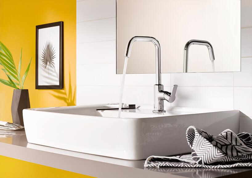 odkręcana wysoka bateria łazienkowa na tle żółtej ściany