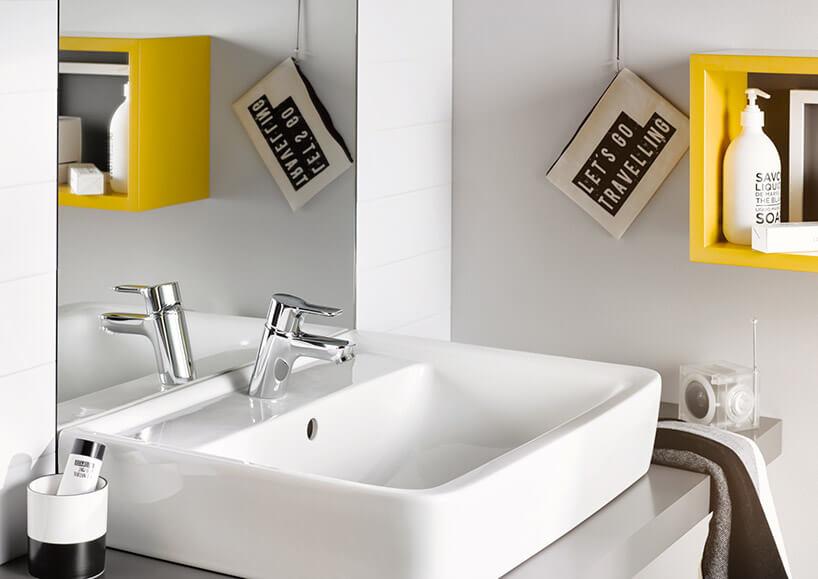 biała umywalka zmałą baterią na tle dużego lustra