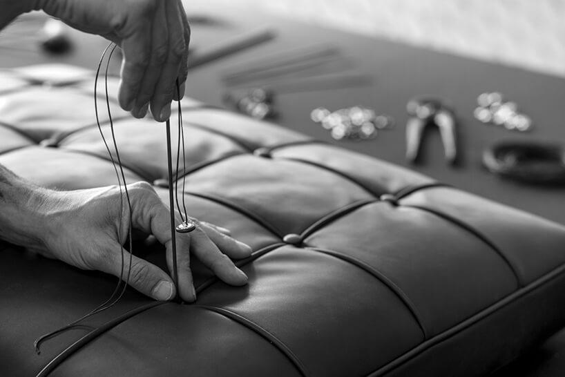 czarno-białe zdjęcie przeszywania siedziska guzikami podczas produkcji krzesła Barcelona
