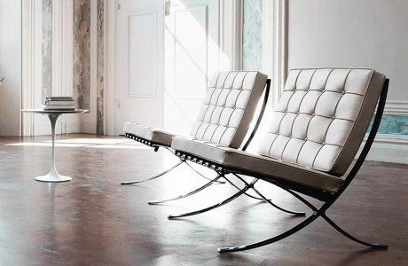 Bauhaus dwa białe krzesła Barcelona Chair, projetu Mies van der Rohe z 1929