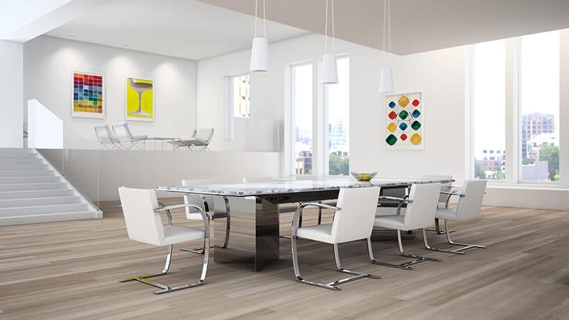 duże białe pomieszczenie zjasnobrązowymi panelami oraz zstołem ikrzesłami wkolorze białym