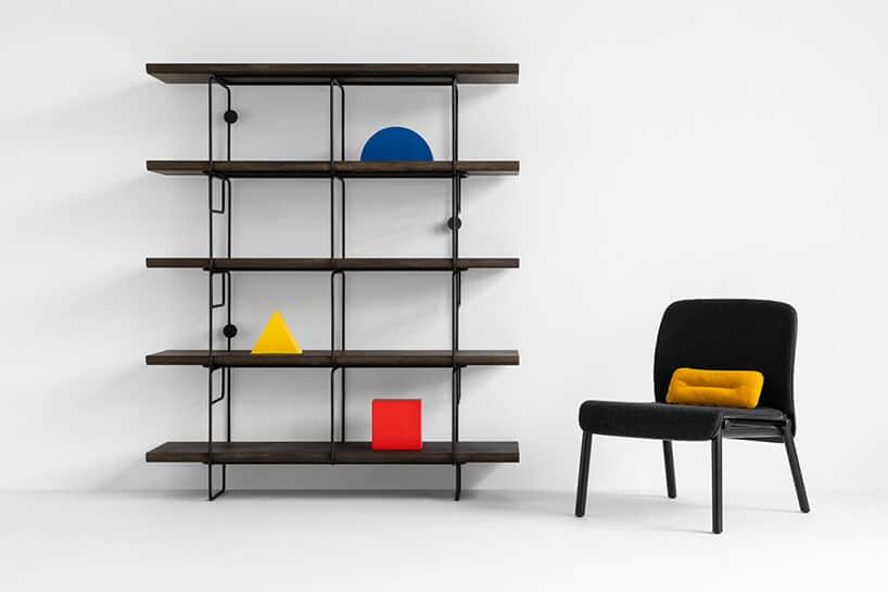 ciemno dębowe półki na regale zmetalu oraz krzesło wczarnym kolorze zżółtą poduszką
