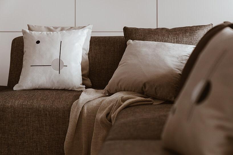 szara kanapa zjaśniejszymi poduszkami oraz ścianą wtle zpłytek