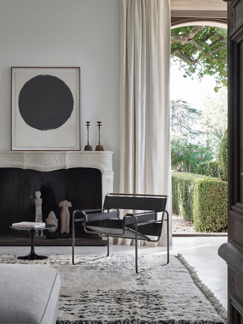 biały salon zczarnym krzesłem Wassily Chair na tle białego kominka