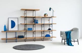 regał przymocowany do ściany z czarną metalową konstrukcją drewnianymi półkami i niebieskimi dodatkami