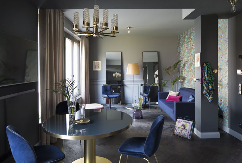 niebieskie krzesła niebieska sofa okrągły stolik prostokątne lustra szare filary weleganckim pokoju