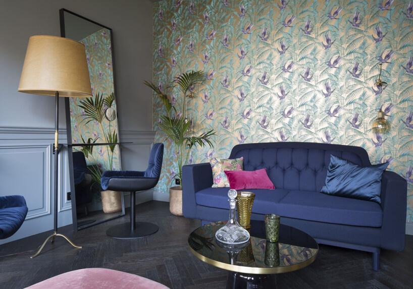 przeźroczyste żółte izielone szklane naczynia granatowa sofa różowa poduszka granatowe fotele lampa zżółtym abażurem ilustro na tle ściany wpaprocie