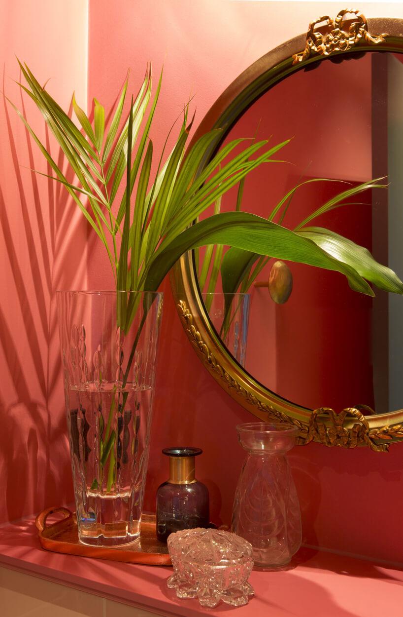 lustro łazienkowe szklane naczynia na tle różowej ściany