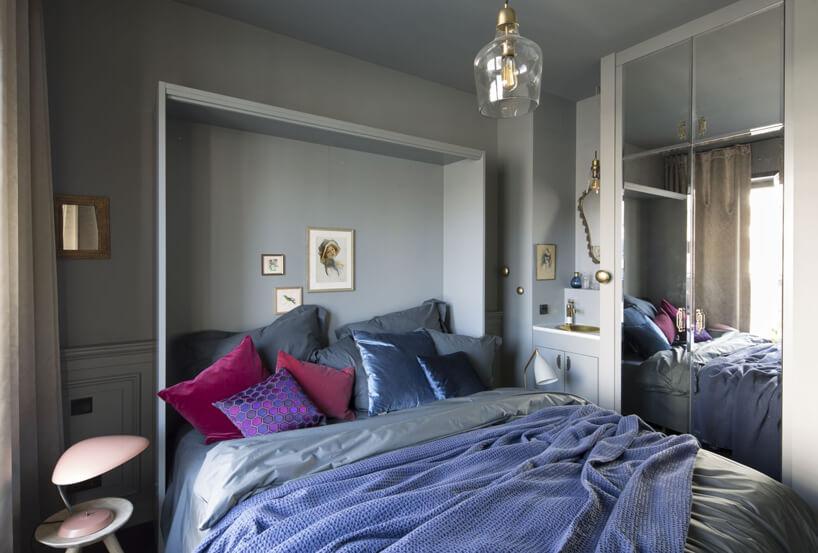 łóżko małżeńskie zniebieską narzutą szafka zlustrem na jasno niebieskiej ścianie