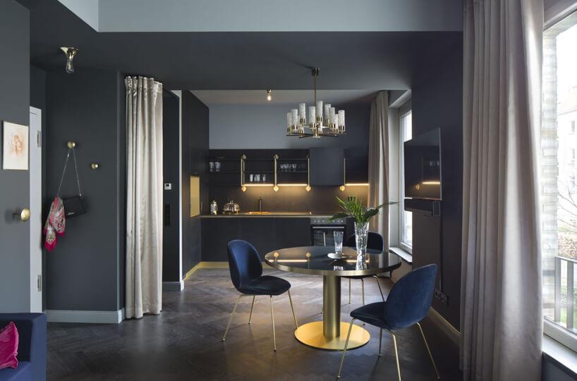 stół kuchenny niebieskie krzesła szary aneks kuchenny na tle szarej ściany