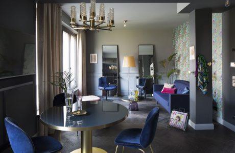Niebieskie krzesła niebieska sofa okrągły stolik prostokątne lustra szare filary w eleganckim pokoju