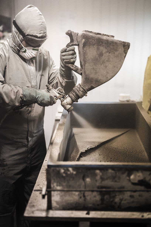mężczyzna wskafandrze podczas pracy rozpylając beton wformie