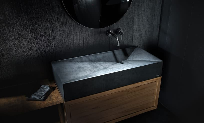 elegancka czarna betonowa umywalka znieregularnej formie wewnątrz na czarnym blacie z
