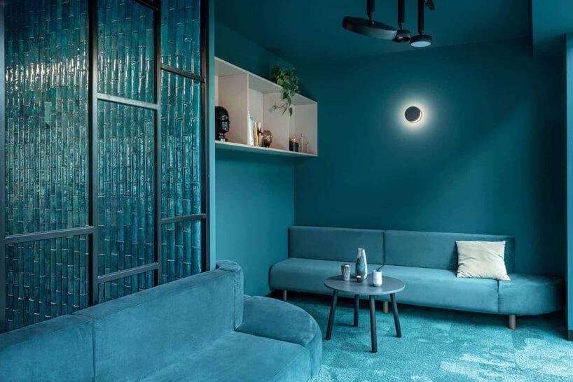 niebieskie wnętrze The Nest od Beza Projekt zwygodnymi sofami imałym stolikiem