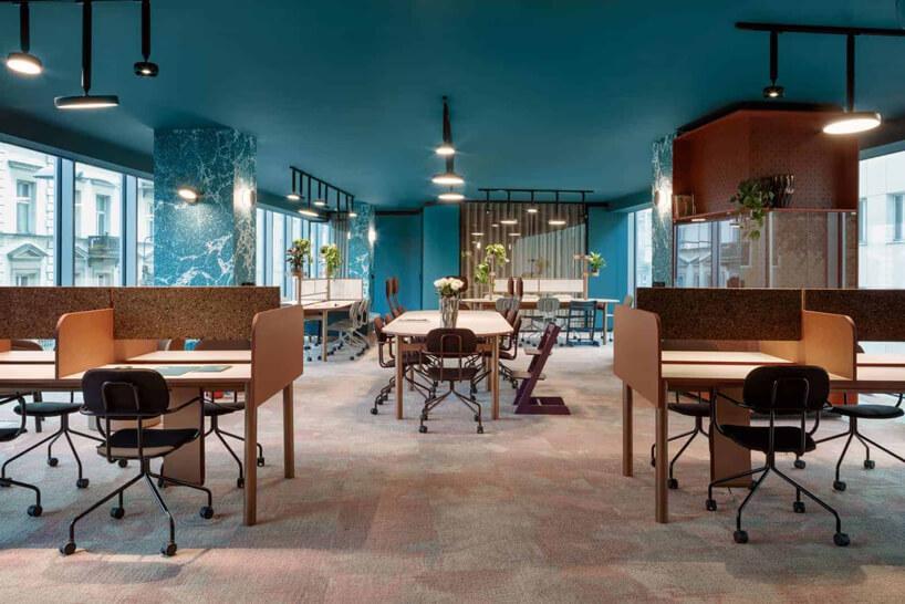 niebieskie wnętrze The Nest od Beza Projekt przestrzeni biurowej zdrewnianymi biurkami stołami ikrzesłami wopen space