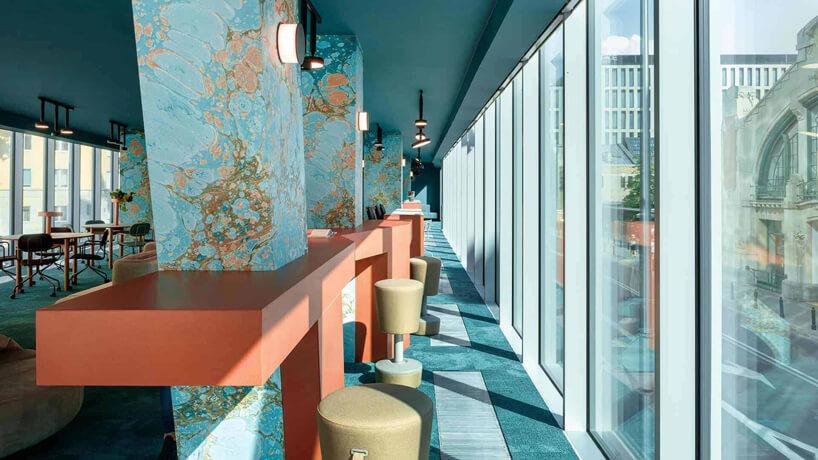 niebieskie wnętrze The Nest od Beza Projekt przestrzeń jadalna zwysokim stolikami przy filarach