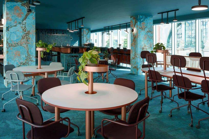 niebieskie wnętrze The Nest od Beza Projekt przestrzeń jadalni zokrągłymi stolikami ifotelami na kółkach